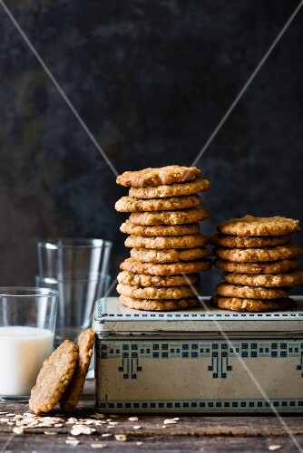 Stacks of Anzac biscuits on a biscuit tin