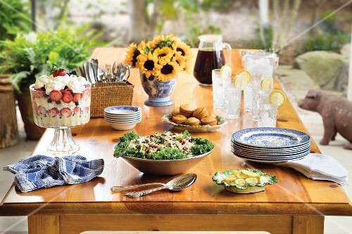 Dried cranberry coleslaw on buffet table with strawberry dessert, corn muffins, iced tea and sunflowers
