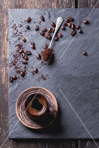 Kaffee in brauner Keramiktasse, frisch gemahlener Kaffe und Kaffeebohnen auf Schieferplatte