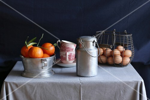 An arrangement of clementines, vintage coffee cups, an aluminium milk jug and eggs