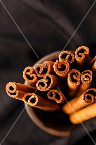 Cinnamon Quills are stacked in an iron mortar