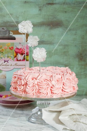 A pink birthday cake on a cake stand