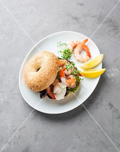 A bagel with prawns and radish