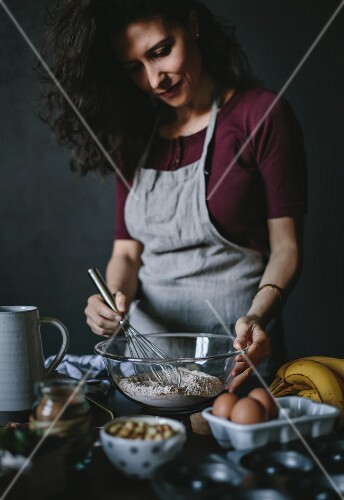 A woman is whisking the dry ingredients for banana bread donuts