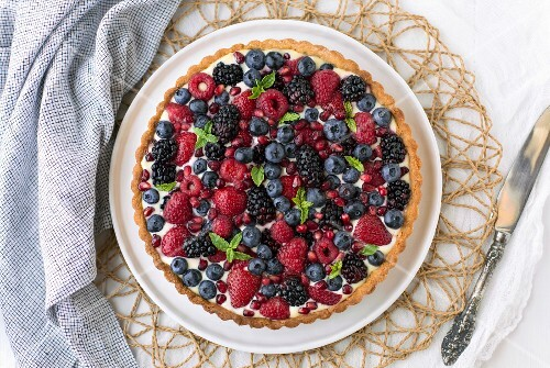 A summer berry tart on a white board