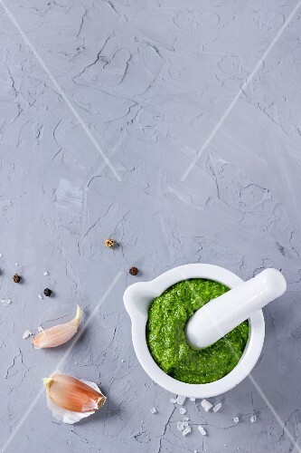 Homemade ramson green pesto sauce in white ceramic mortar with pestle over gray textured background
