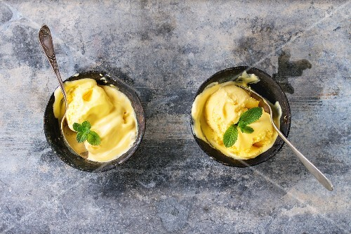 Homemade mango ice cream with fresh mint in vintage iron bowls over gray metal textured background