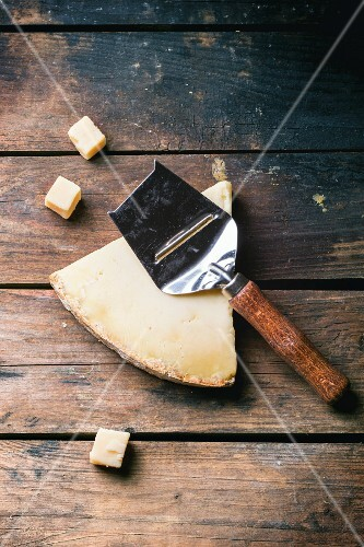 Big piece and little cubes of Belgian cheese with cheese knife over wooden background