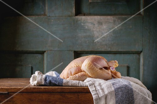 Raw mini Chicken on kitchen towel over old wooden table