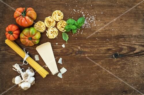 Spaghetti, olive oil, garlic, Parmesan cheese, tomatoes and fresh basil on black slate background