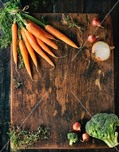 Wooden healthy food background with raw vegetables and herbs (carrots, onions, broccoli and thyme)