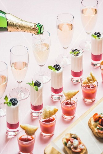 Various snacks, brushettas, gazpacho shots, desserts with berries and champagne pouring to glasse