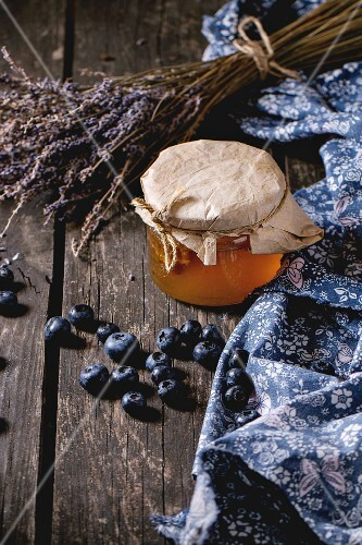Glass jar of liquid honey with honeycomb inside, fresh blueberries and bunch of dry lavender over old wooden table