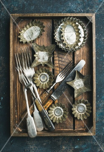 Old vintage tin baking molds and cutlery in rustic wooden tray over dark blue shabby background