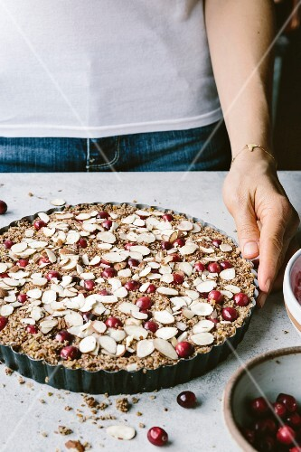 A woman with a cranberry almond tart before it went into the oven