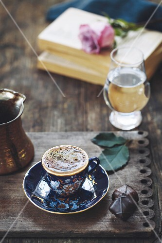 A cup of Turkish coffee with foam on top is photographed on a vintage wood plate