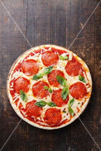 Pepperoni Pizza with basil leaves on wooden table