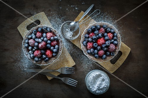 Berry tartetelets with icing sugar in baking dishes on wooden plates with sifter and cake forks