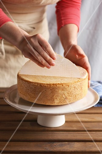 Female hands peeling the parchment paper from the bottom of the sponge cake