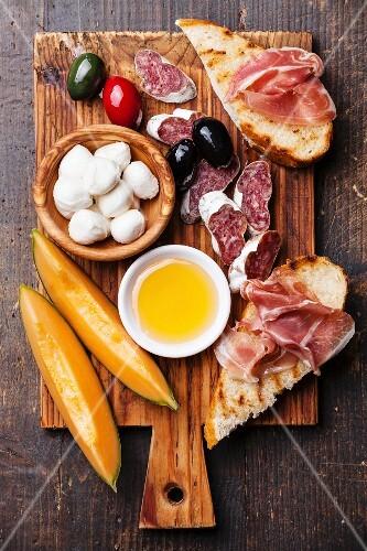 Prosciutto ham, Slices of melon cantaloupe, Mozzarella cheese and Olives on cutting board