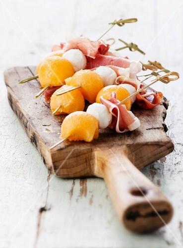 Mozzarella, prosciutto, melon canapes on textured background