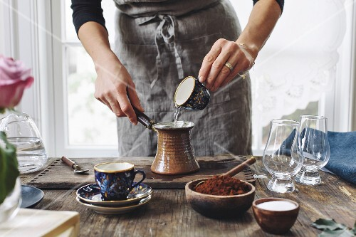 A woman is pouring water into a small pot to make Turkish Coffee