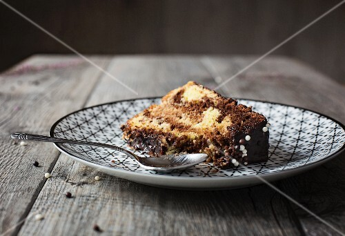 Slice of marble chiffon cake with chocolate frosting on grey table
