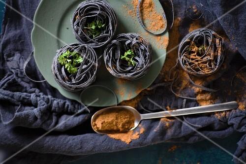 Schwarze Bandnudeln mit Petersilie und verschüttetem Gewürz auf schwarzem Tuch