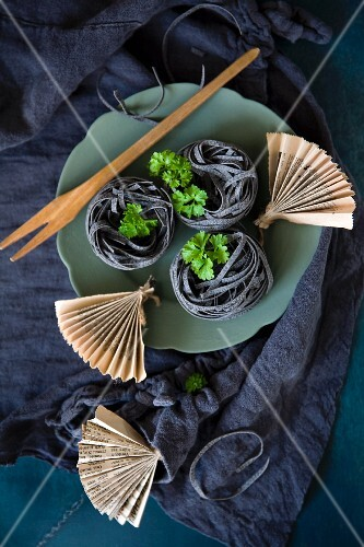Black ribbon noodles with parsley and small newspaper fans on a turquoise plate