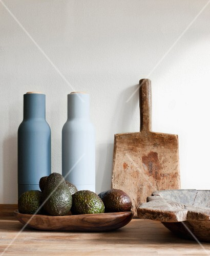 Ecology and Soft Colours. Close up of a wooden board, a wooden bowl of avocados and two pottery jars