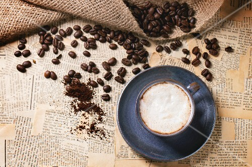 Blue ceramic cup of cappuccino with roasted coffee beans over old newspaper