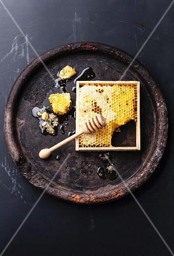 Honigwabe mit Honiglöffel auf Vintage Untergrund