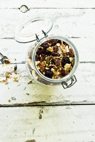 Cereal with pecans, pumpkin seeds, cranberries and oat flakes in a glass