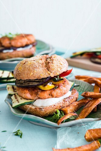 A salmon burger with grilled vegetables and sweet potato pancakes