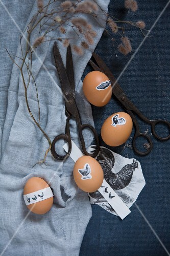 Easter eggs with animal motif stickers on a blue cloth with vintage scissors
