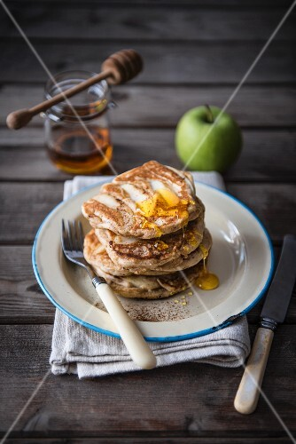 A stack of apple pancakes with honey.