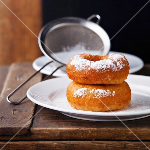 Sweet donuts with powder on black background