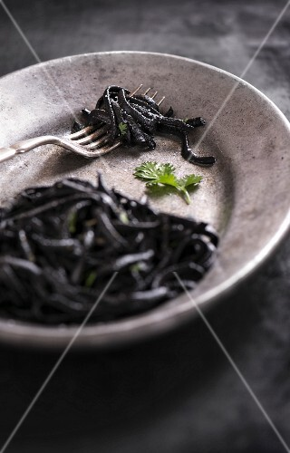 Squid ink pasta with fresh cilantro on a metal plate with antique fork