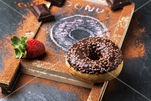 Chocolate and drawing donuts with fresh strawberries and dark chocolate served on chalkboard