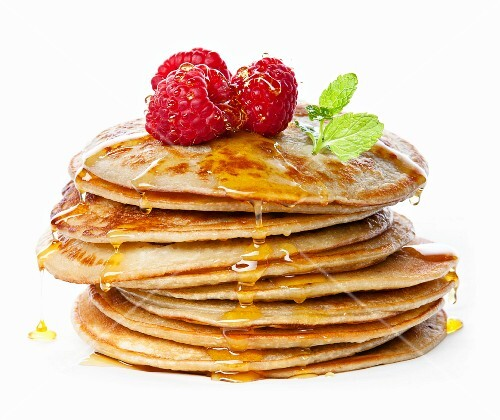 Small pancakes topped with honey, raspberries and mint on white background