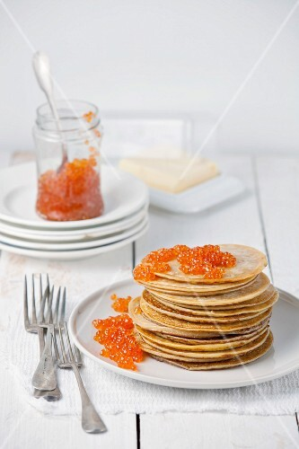 Pancakes with red caviar on white wooden background