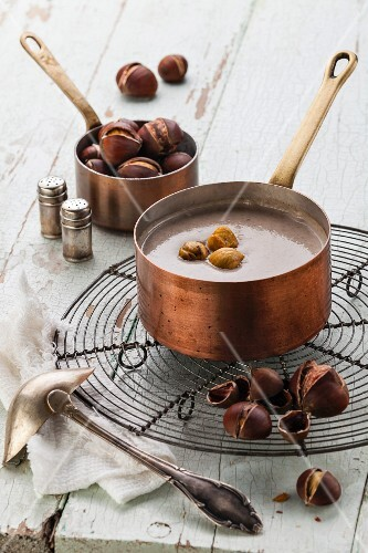 Chestnut soup in copper pot with roasted chestnuts on blue textural background
