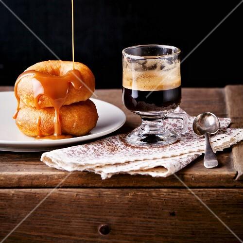 Zwei Donuts mit Karamellsauce, dazu ein Kaffee im Glas
