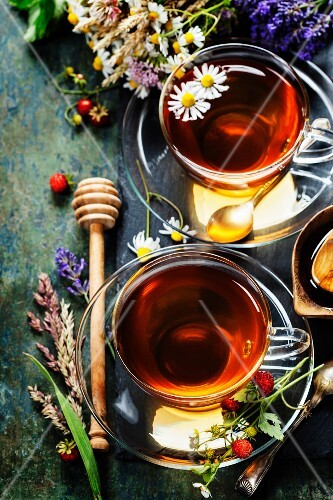 Herbal tea with honey, wild berry and flowers on wooden background