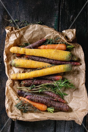 Heap of colorful raw carrots with fresh thyme herbs on paper bag over black wooden surface
