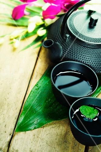 Asiatischer Tee in Schälchen und Teekanne auf Holztisch