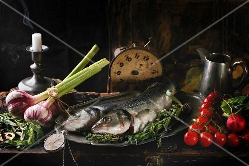 Stillleben mit rohem Seebarsch, Kräuter, Gemüse und Vintage-Uhr