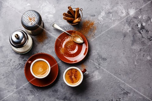 Coffee cup with cinnamon on gray concrete stone background