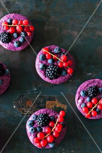 Vegan raw berry tarts on a black background