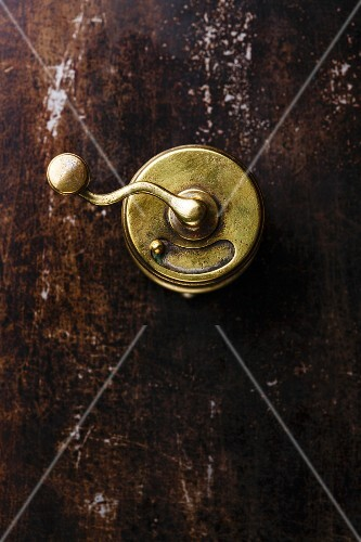 Pepper mill on old scratched metal black dark background texture